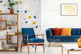 sessel und sofa mit kissen in blau und orange wohnzimmer interieur mit poster und pflanze echtes foto stockfoto und mehr bilder blau