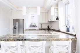 modern weiße küche mit langer arbeitsplatte aus granit