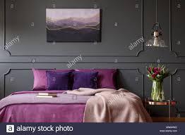 decke auf lila bett neben tisch mit blumen im schlafzimmer