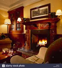 wall lights on either side of carved wooden fireplace in cosy