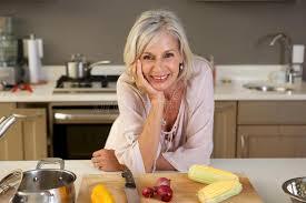femmes plus cuisine une femme plus âgée se penchant sur le comptoir de cuisine