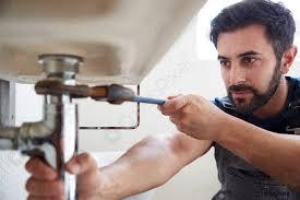 foto auf lager klempner mit schraubenschlüssel um undichtes waschbecken im badezimmer zu reparieren