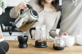 Midsection Of Woman With Boyfriend Making Coffee At Table In Kitchen