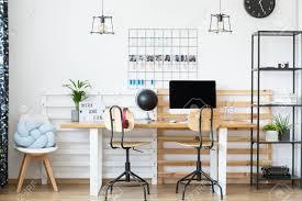 zwei klassische stühle am holztisch mit dem desktop und der schwarzen kugel in inspirierendem arbeitsplatz