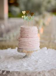 Pink Wedding Cake With Ruffled Icing And Gold Glitter Heart Toppers