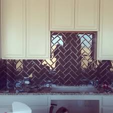 glass subway tile backsplash and herringbone pattern on