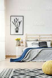 schwarz weißkaktusplakat hängt an der wand innen helle schlafzimmer mit gelben blumen doppelbett und gemusterten teppich stockfoto und mehr bilder