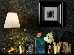 Wallpaper Provides A Backdrop For Gold Coloured Lamp Stand Plant Pot And Clock