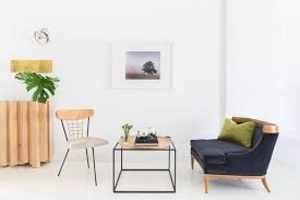 A Minimal Sitting Room Featuring Epoxy Floors With Photo Hung Below Eye Level To