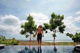 100 Infinity Swimming Asian Man Standing On Edge Of Infinity Swimming Pool Stock Photo