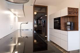 weiße küche mit grifflosen fronten und dunkler arbeitsplatte