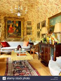 Richly Patterned Wallpaper On Walls And Ceiling In Old Fashioned Drawing Room With Antique Sideboard