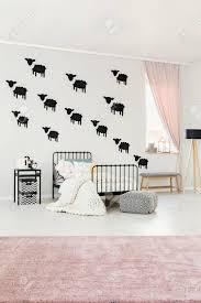 kopierter puff rosa teppich und weiße strickdecke auf bett im schlafzimmerinnenraum des hellen kindes mit schafwandaufklebern und grauer bank