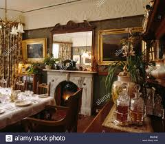 Mirror Above Fireplace In Victorian Dining Room With Gilt Framed Pictures And Ornate Plasterwork Cornice