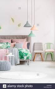 verschiedene stühle neben kingsize bett mit grün und rosa