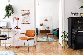 stylish compositon of retro home interior with mock up poster frame vintage orange chair piano furnitures design ls gold shelf plants and