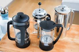 Four Black And Silver French Presses Sitting On A Wooden Countertop
