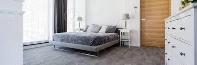 sehr ruhig modernes schlafzimmer in grau mit teppichboden ein großes bett und große fenster mit jalousien