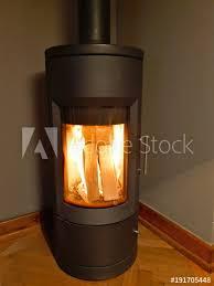 ein moderner brennender schwarzer eiserner kaminofen mit