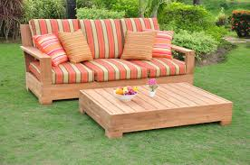 Wooden Sofa With Stripped Orange And Cream Sunbrella Cushions Plus Rectangle Table On Green Grass