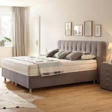 boxspringbett im grauem textilstoff mit silbernen füßen