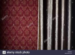 Front View Close Up Detail Of Light Cream Colored Curtain Covering Red Wallpaper Wall With Classic