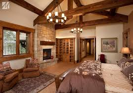 Rustic Master Bedroom With French Doors Chandelier Stone Fireplace Exposed Beam Wood