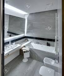 bad in einem modernen stil mit den weißen und grauen fliesen gefliest es gibt ein weißes waschbecken mit zubehör spiegel bad handtuchhalter