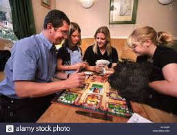 A FAMILY PLAYING CLUEDO BOARD GAME IN THEIR LIVING ROOM