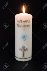 Lit white christening candle with blue detail on black background Stock