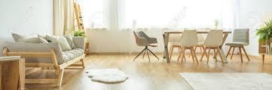 weißer teppich auf bretterboden nahe einem beige sofa im hellen esszimmer mit weißen und grauen stühlen am tisch