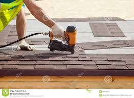 Wood Floor Nailer Gun by Construction Worker Putting The Asphalt Roofing Shingles With Nail