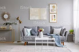 grauen sofa mit kissen und decke im hellen wohnzimmer interieur mit gold le frische blumen auf weißen tisch und teppich auf dem boden stehen