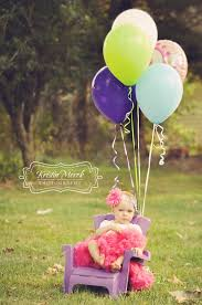 Little girl poses in a tutu with balloons for her first birthday photos