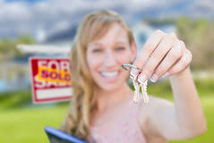 Excited Woman Holding House Keys And Sold Real Estate Sign In Fr Stock Image