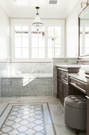 brown and gray bathroom with clear beaded chandelier over tub
