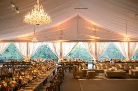 Tent Wedding In Texas With Chandeliers Lighting Long Rustic Wood Tables And Low
