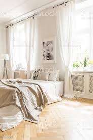 beige decke auf dem bett und poster in weiße schlafzimmer innenraum mit vorhänge am fenster echtes foto stockfoto und mehr bilder beige