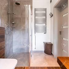 stilvolles badezimmer mit hölzernen details und modernen neuen dusche mit glastür