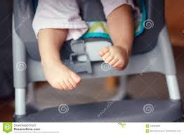 Chubby Baby Legs Feet. Small Kid Sitting In High Chair Stock Photo ...
