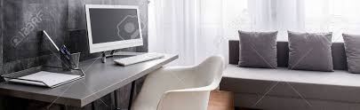 stilvoll dekorierte büro mit schreibtisch und computer in der modernen geräumigen wohnzimmer