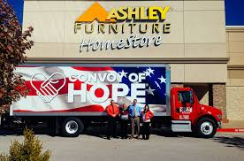 Employees At A Regional Ashley Furniture HomeStore Stand In Front Of Convoy Hope Truck