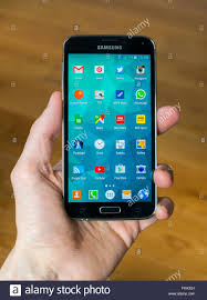 A hand holding a Samsung S5 phone with the home screen open