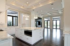 Traditional open layout kitchen with white cabinets and marble counters
