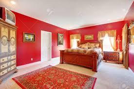 große rote schlafzimmer mit alten bett und zwei fenster
