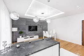 modernes wohnzimmer mit abgehängter decke tv len und betonwand