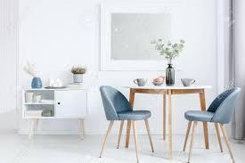 kleiner esstisch mit zwei gepolsterten stühlen und einem weißen schrank in einem hellen offenen wohnzimmer
