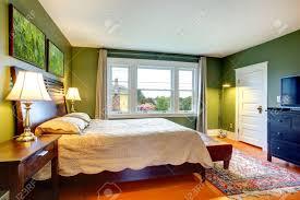 grüne wände schlafzimmer mit hohem kopfteil bett ottaman schwarz schrank mit fernseher teppich