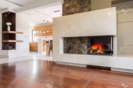 marmor kamin in einem großen wohnzimmer mit getäfelten boden verbunden mit hellen küche