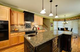 with black appliances and maple cabinets